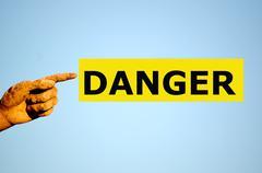 Stock Photo of finger with rectangular yellow label DANGER