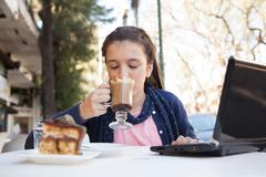 Girl in the street drink a capuccino - stock photo