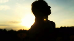 A silhouette of a woman  on a sunset turns her head and dancing - stock footage