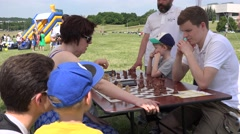 Family with children play chess in free outdoor tournament. 4K Stock Footage