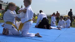 Stock Video Footage of boy make aikido training exercise on tatami in park. 4K