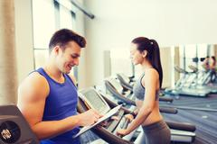 Happy woman with trainer on treadmill in gym Stock Photos