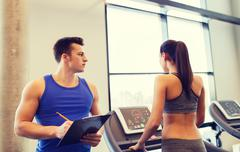 Woman with trainer on treadmill in gym Stock Photos