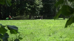 Worker ride lawn mower tractor and young couple in park. 4K Stock Footage
