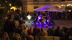 Band play guitar and woman spin big whirligig in park evening . 4K Stock Footage