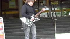 Man play electrical bass guitar in street. Zoom out. 4K Stock Footage