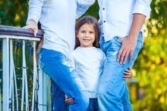 very cute little blonde girl holding the foot mom and dad. hug - stock photo