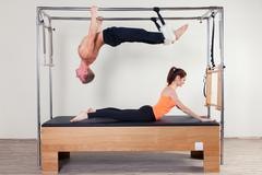Pilates aerobic instructor woman and man in cadillac fitness exercise Kuvituskuvat