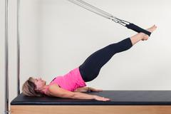 Pilates aerobic instructor woman in cadillac fitness exercise Stock Photos
