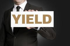 yield sign held by businessman concept - stock photo