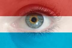 Eye looks through Luxembourg flag background concept macro - stock photo