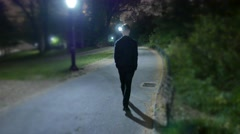 one man walking alone trough city park at night. spooky scary silhouette shadow - stock footage
