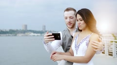 Young mixed couple sitting on bench outdoors looking at smart phone tablet Stock Footage