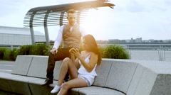 Boyfriend and girlfriend sitting together outdoors watching smart phone Stock Footage