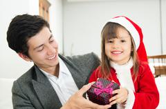Cute little girl receiving present from dad - stock photo