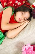 Sweet little girl dressed in Christmas dress sleeping Stock Photos