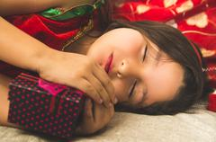 Little girl sleeping next to Christmas present Stock Photos