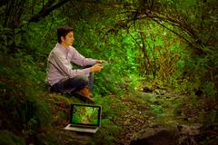Young handsome man with internet connectivity in the jungle Stock Photos