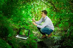 Young handsome man with great internet connectivity in the jungle forest Stock Photos