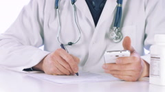 Doctor hands halding a smart phone and writing prescription Stock Footage