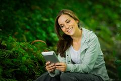 Beautiful young girl holding a tablet enjoying excellent connectivity in the - stock photo