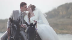 Bride and groom riding on horses at the seashore (wedding day) Stock Footage