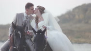 Stock Video Footage of Bride and groom riding on horses at the seashore (wedding day)