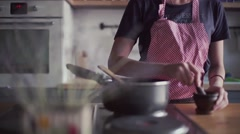 Young girl in apron preparing food in kitchen - stock footage