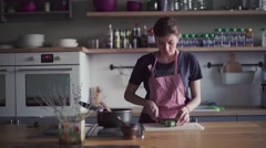 Young girl in apron preparing food in kitchen Stock Footage
