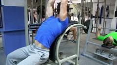Group people in gym. Man working on the trainer at the gym. In the background a - stock footage