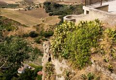 View down the steep rockface to valley in Ronda Stock Photos