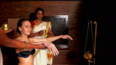 Hindu beautician pouring milk on the white woman body in the spa salon Stock Footage