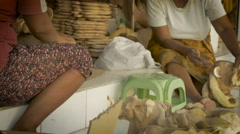Dolly shot of two Asian women sanding wooden sculptures by hand Stock Footage