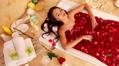 The girl takes a bath with rose petals. The camera moves from the face to the Stock Footage
