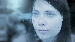 Thoughtful women looking trough window on a rainy day. sad depressed person Stock Footage