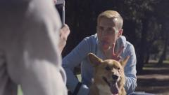 Man Sticks Out His Tongue, Gives His Corgi Dog Bunny Ears For Photos, In Park Stock Footage