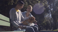 Gay Couple Enjoy A Sunny Day In The Park With Their Corgi Dog Stock Footage