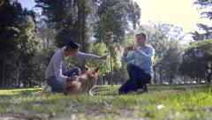 Man Uses Treat To Get His Dog To Sit For Photos With His Boyfriend Stock Footage