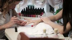 Woman in a nail salon receiving a manicure by a beautician Stock Footage