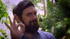 Portrait of a bearded man saying A-OK with his right hand - stock footage