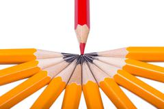 Red sharpened pencil among non sharpened yellow Stock Photos