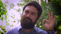 Portrait of a bearded man saying A OK with his left hand Stock Footage