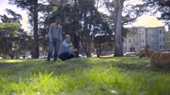 Gay Couple Play Fetch With Their Corgi Dog In Dog Park Stock Footage