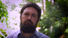 Portrait of a bearded man forcing a smile by using his hands - stock footage
