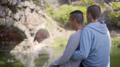 Back Of Cute Gay Couple Holding Each Other, Enjoying View Of Duck Pond Stock Footage