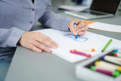 Female Artist Draw on a Paper at the Table Stock Photos