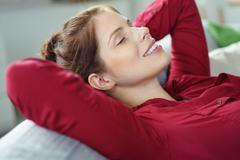Blissful woman relaxing on a sofa at home - stock photo
