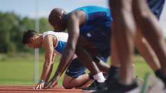 4K Group of athletes at running track, crouch at starting line before a race - stock footage