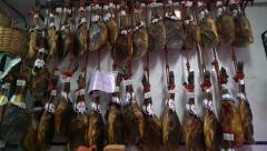 Stock Video Footage of Panning left shot of legs of Iberian ham in a shop in Andalusia, Spain.