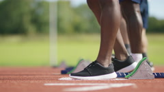 4K Group of athletes at running track, crouch at starting line before a race Stock Footage